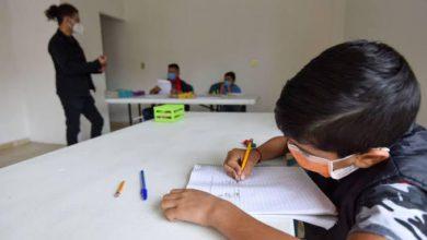 niño dibujando con cubrebocas en escuela particular guardando sana distancia