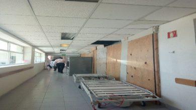 Pasillo de hospital con tarimas y material de construcción a la vista