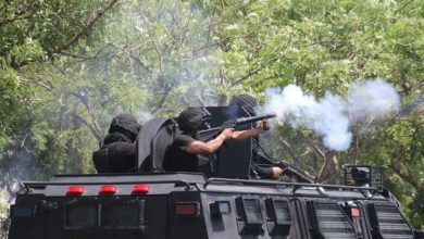 Policías estatales lanzando gas lacrimógeno contra estudiantes