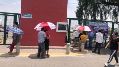 Familiares de adultos mayores con sombrillas con el logo de Morena