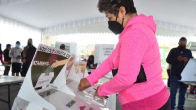 Mujer vestida con sudadera rosa votando